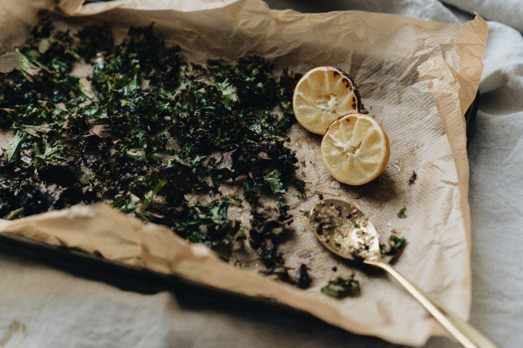 cải kale xanh kho, 2 trái chanh nhỏ màu vàng và chiếc muỗng