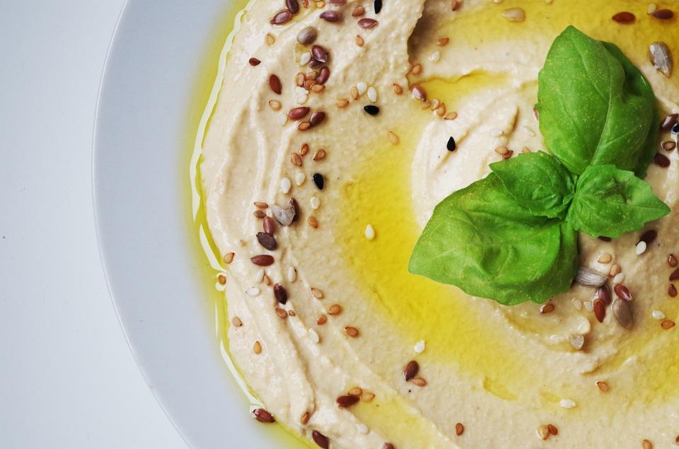 đĩa hummus vàng với lá gia vị trang trí