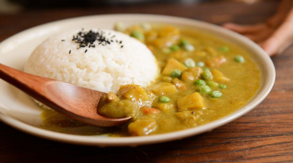 Cơm nấu chín và thức ăn cà ri dọn ra đĩa trắng