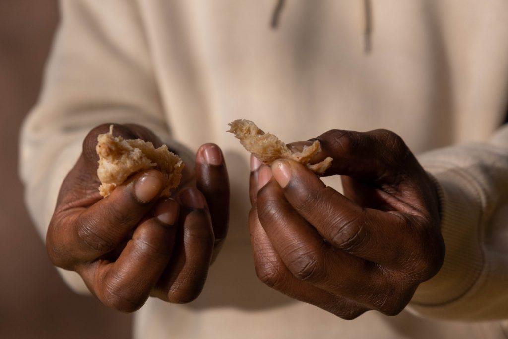 Người cầm bánh mì nâu với kem trắng