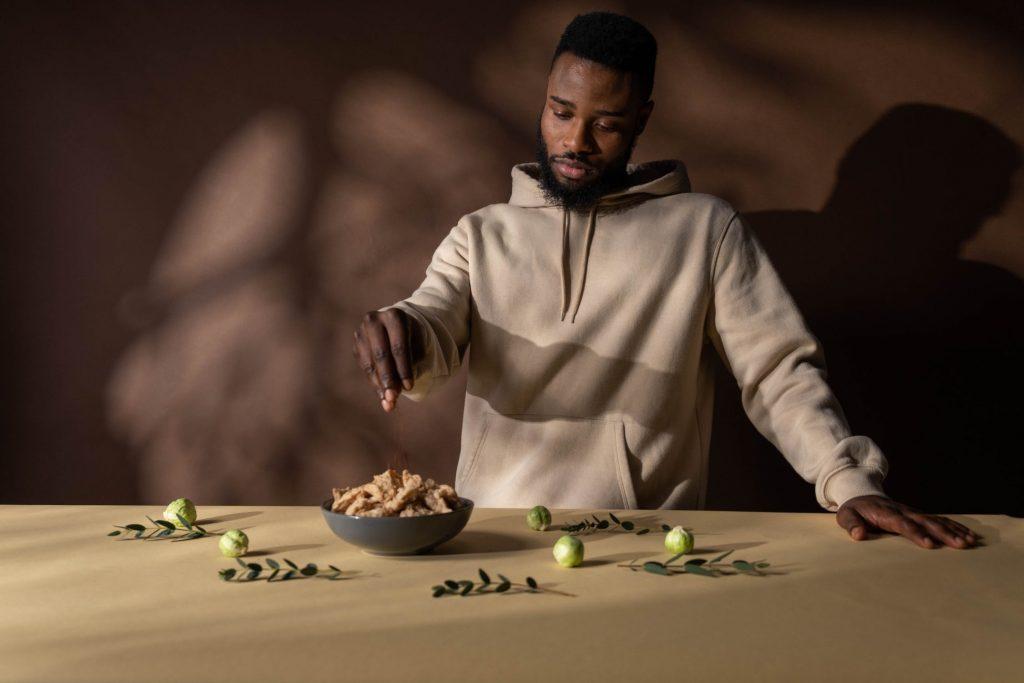 Người đàn ông mặc áo hoodie trắng đang ăn